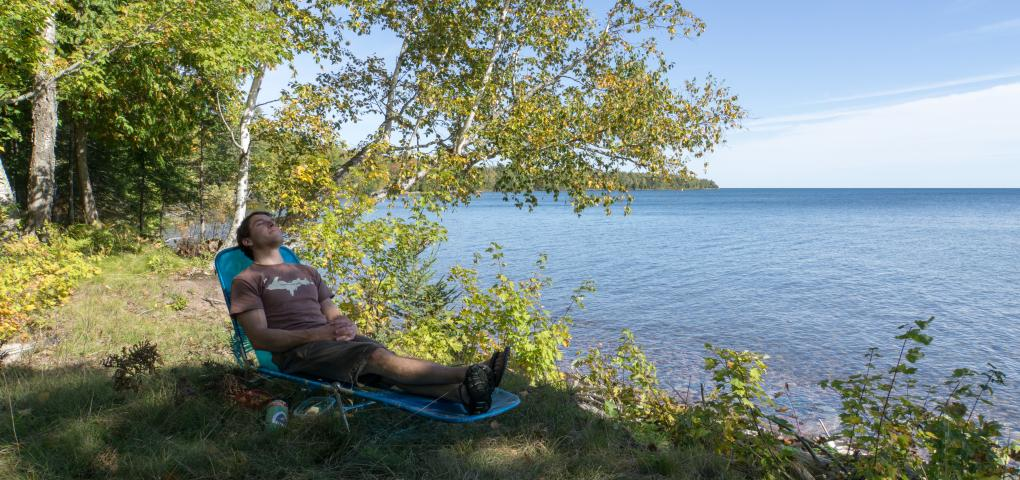 Nathan MIller relaxing on shore on lounge chair with blue water behind