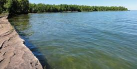 long bedrock shoreline curving toward point sticking out on Lake Superior