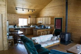 inside of main cabin with wood paneling and open ceiling