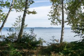 view of huron mountians in the distance with Lake Supeior waters showing through the trees on shore