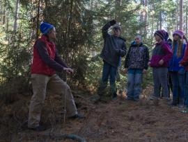 Pat teaching elementary students about soils among the large hemlocks