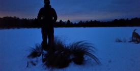 person looking out over a frozen lake in winter twilight