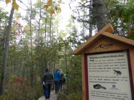 A trail sign in foreground and two people hiking in background