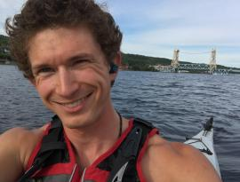 Photo of AmeriCorps member Nick Potter in kayak with Portage Lift bridge in background
