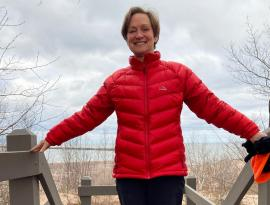 carolyn meingast by shore of L Superior with bright winter coat smiling